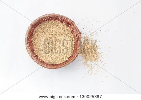 Millet bird's food inside a wicker basket and some scattered outside the basket on isolated white background
