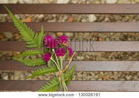 Pink flower tied together with green leaves on a wooden bench.