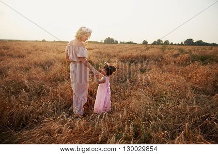 mother and daughter run on the field. Long dresses. The haystack
