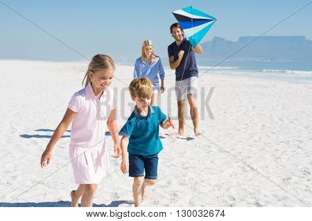 Happy family running at beach with blue kite. Family playing with kite in a summer vacation. Smiling family flying kite together at seaside.