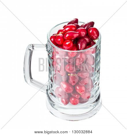 Riped dogwood berries in beer mug. Isolated on a white background.