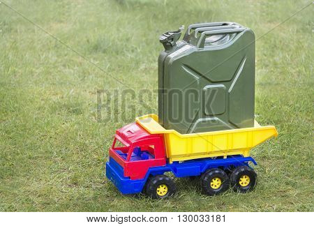 Toy car the truck with grenn canister on a gren grass
