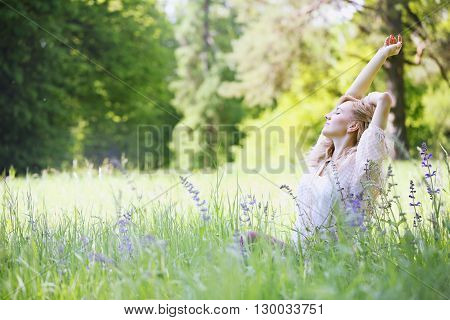 Young beautiful girl sitting in the grass, stretching after waking up