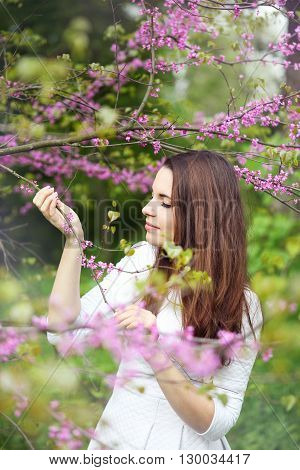 Beautiful woman smelling the flowers on the tree