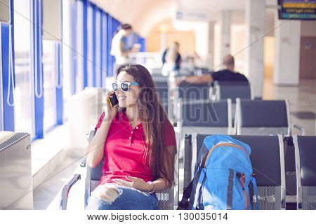 Young female passenger on smart phone at gate waiting in terminal while waiting for her flight. Air travel concept with young casual woman sitting with hand luggage backpack