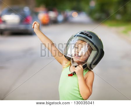Happy kid playing in helmet outdoors. Travel and fun concept