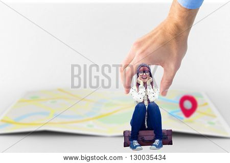 Smiling hipster woman sitting on suitcase against map