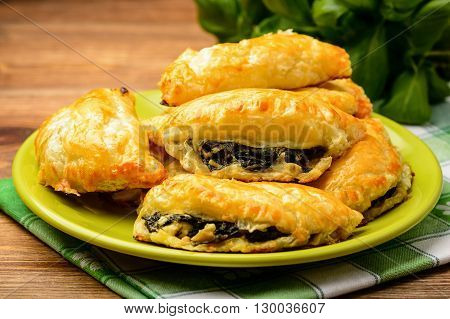 Puff pastries with spinach and cheese .