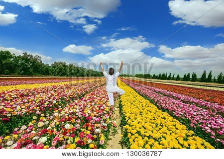 Delighted woman in white greets the rising sun. Flower kibbutz near Gaza Strip. Spring flowering buttercups