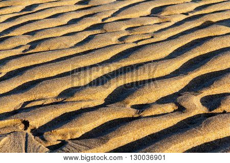 Sand On The Beach With Ripples Left By The Sea