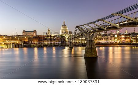 Millennium Bridge and St. Pauls church in London at sunset