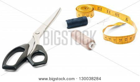 Tailors tools - scissors, spool of thread and tape measure on white