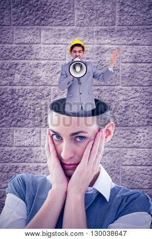 Architect with hard hat shouting with a megaphone against image of a wall