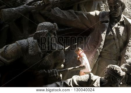 Kyiv, Ukraine - May 8, 2009: Little girl plays among scupltures of soldiers that are part of a soviet monument at the Museum of The History of Ukraine in World War II in Kyiv