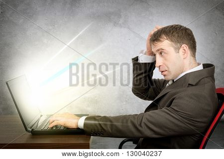 Serious man in suit sitting at table and typing on laptop with light coming through screen