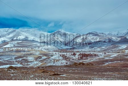 Altai mountains with snow and clouds kosh-agach. Severe mountains peaks covered by snow. Russia Siberia Altai mountains Chuya ridge.