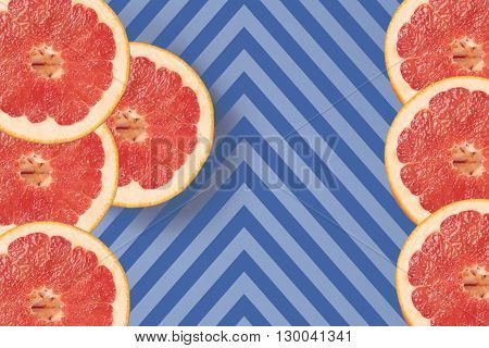 Bright red grapefruit on diagonal lines texture top view. Striped background in blue and dark blue stripes. Lot of red grapefruits located top left. Lines texture. Diagonal lines.