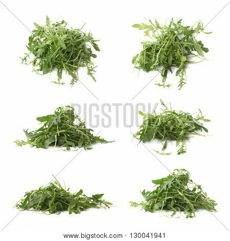 Pile of eruca sativa rucola arugula fresh green rocket salad leaves, composition isolated over the white background, set of six different foreshortening compositions