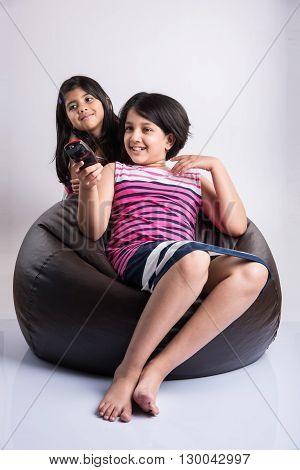 two little indian girls watching tv or television and switching channels with remote control, two cute asian girl with TV remote control in hand