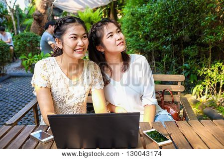Smiling Women Friends With Hot Drink Using Laptop In Cafe