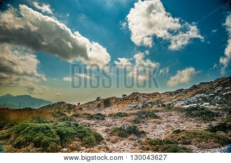 Beautiful landscape with rocky mountains and clouds on the western part of Mallorca island, Spain.  Tramuntana mountains with green bushes. Tourist trekking destination in Spain.