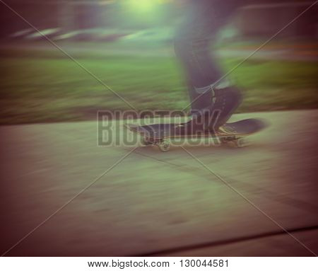snapshot type ultra 70s image of a guy at the skate park with a motion blur in a dark city toned with a retro vintage instagram filter app or action effect