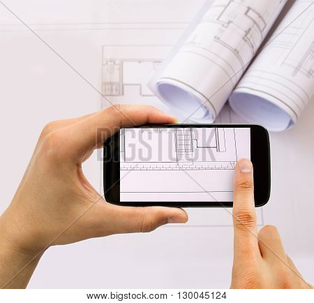 businessman taking photo of plans with smartphone in connection with industrial espionage