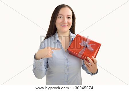 smiling woman holding a present and pointing it with her finger on a white background