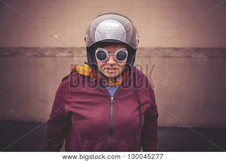a woman in a motorcycle helmet with steampunk goggles on in front of a wall toned with a retro vintage instagram filter effect app or action