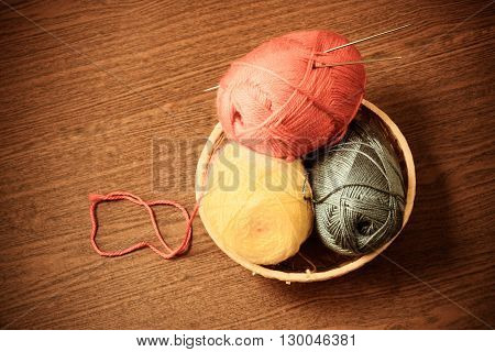 Skeins of yarn in a basket with knitting needles on wooden background. Vintage style