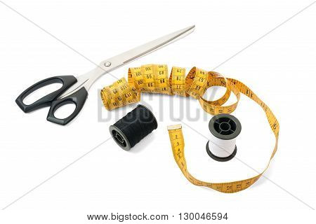 Sewing accessories: thread bobbin, measure tape and scissors on white background