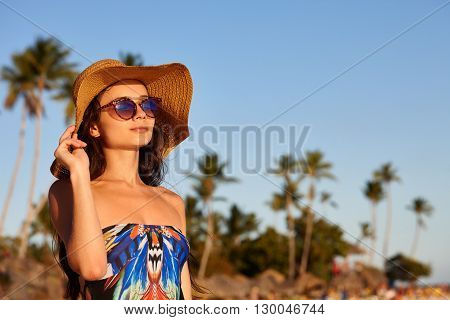 Beach vacation. A beautiful woman in sunglasses and sunhat standing on a blue sky and palms background.