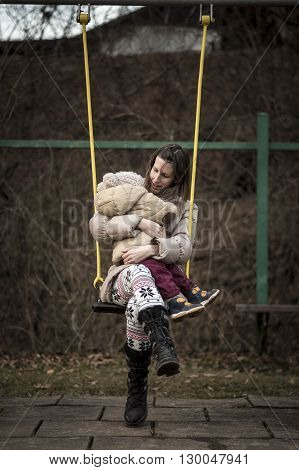 Young mother enjoying on a swing in a park with her toddler in her lap both wearing winter jackets.