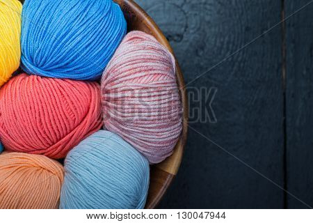 Several clorful knitting yarn balls in basket