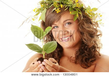 Closeup portrait of a beautiful happy young woman holding plant