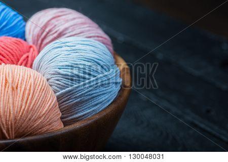Balls of colorful knitting yarn balls in basket