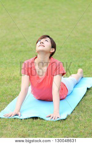 Japanese woman outside doing yoga Cobra Pose