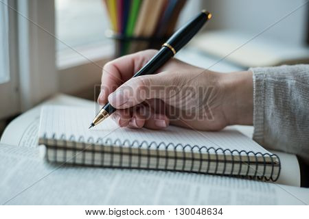Young Woman Writing Memos In Front Of Big Window