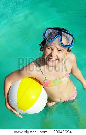 funny little girl in swimming pool. children outdoors