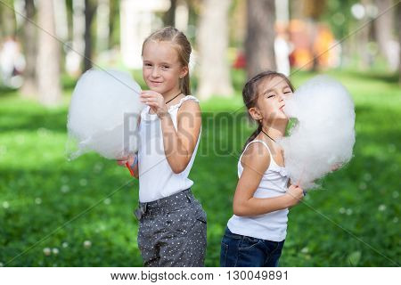 Cute girls with white cotton candy in the summer park