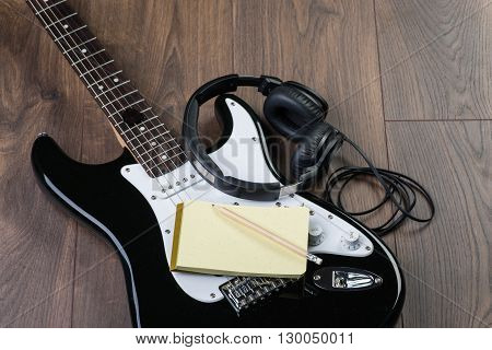 Electric Guitar With Headphones, Notedpad And Pencil On A Brown Wooden Floor