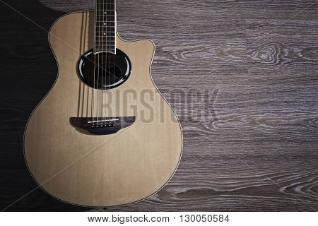 The acoustic guitar on the wooden floor