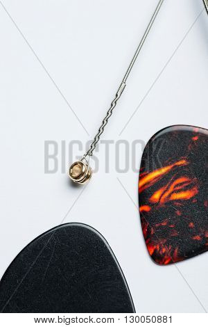 Electric Guitar String With Two Mediators On White Surface