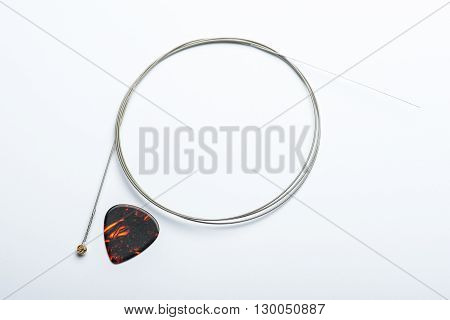 Electric Guitar String With Mediator On White Surface