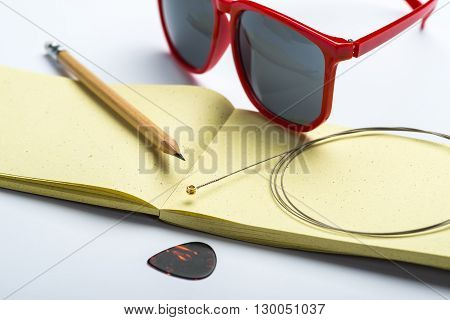 Yellow Notepad With Pencil, Sunglasses, String And Mediator On White Surface