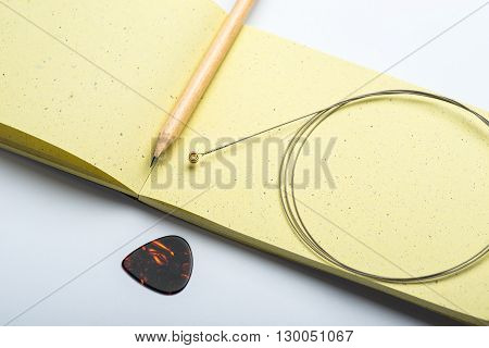 Yellow Notepad With Pencil, String And Mediator On White Surface