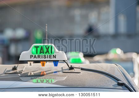 Green taxi sign on roof in Paris France