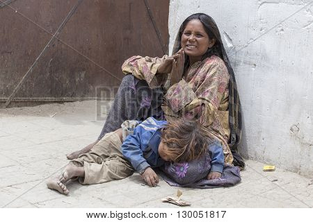 LEH INDIA - JUNE 24 2015: Unknown beggar woman with a child begging near a Buddhist temple in Leh Ladakh. Poverty is a major issue in India
