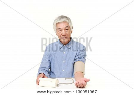 portrait of senior Japanese man checking his blood pressure on white background