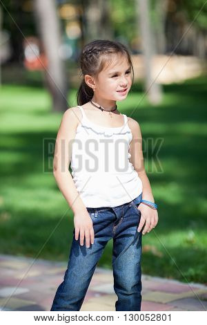 Wonderful happy girl standing on the lawn in the park. Girl seven years.